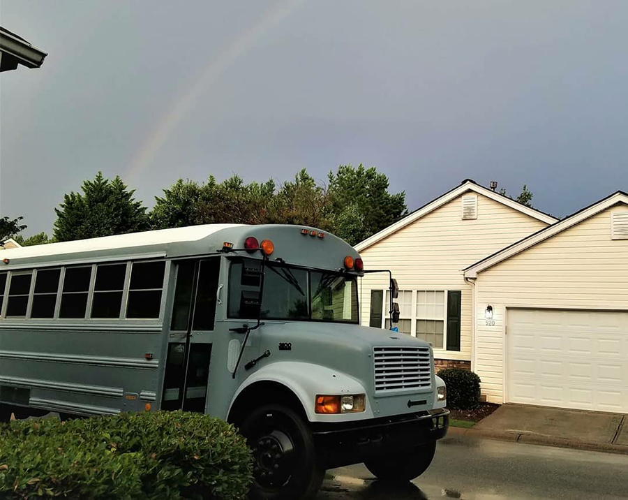 home owner rainbow skoolie bus neighborhood